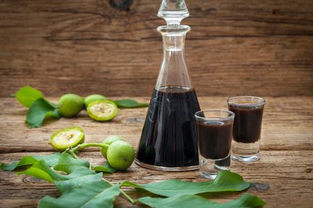 Butelka i dwie szklanki z likierem orzechowym. Domowy likier orzechowy na rustykalne drewniane tła. Zdjęcie Seryjne