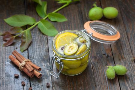 Preparing green walnut liqueur. Homemade  nut liquor full of healthy iodine Фото со стока