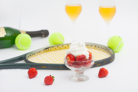 Strawberries with whipped cream, glasses with champagne and  tennis equipment on Wimbledon tournament. Wimbledon Grand slam celebration concept.