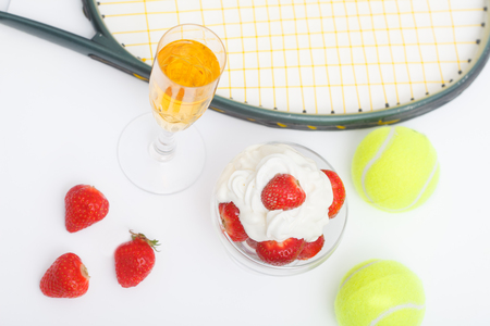 Strawberries with whipped cream, glasses with champagne and  tennis equipment on Wimbledon tournament. Wimbledon Grand slam celebration concept. Top view.