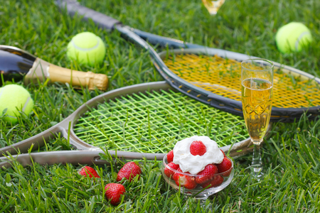 Strawberries with whipped cream, glass with champagne and tennis equipment on Wimbledon tournament grass. Wimbledon Grand slam celebration concept.
