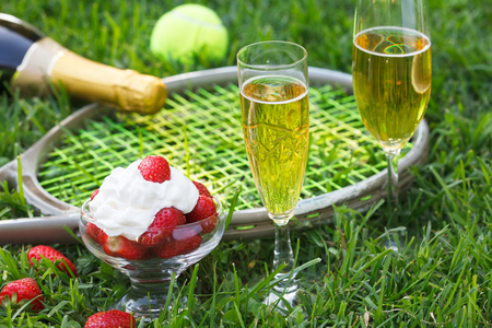 Strawberries with whipped cream, glasses with champagne and tennis equipment on Wimbledon tournament grass. Wimbledon Grand slam celebration concept.