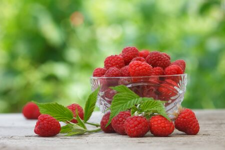 Ripe fresh organic raspberries in crystal glass bowl on wooden table, with green garden for background. Detox raspberry fruit for healthy living style.