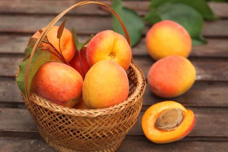 Apricot. Ripe Organic Apricots in wicker basket with fresh leaves on a  wooden table. 写真素材