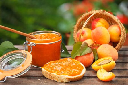 Apricot jam in a glass jar, fresh apricots in a basket on wooden background. Sweet breakfast in nature. 写真素材