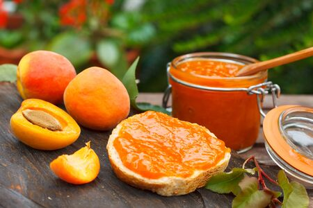 Apricot jam in a glass jar and fresh apricots on wooden background. Bread slice with apricot marmalade for sweet breakfast in nature.