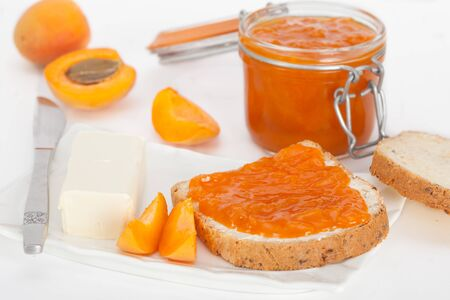 Apricot jam in a glass jar and fresh apricots on a table. Bread slice with butter and apricot marmalade for breakfast.