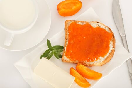 Apricot marmalade and cup of milk on white table. Bread slice with butter and apricot jam for breakfast. Top view.