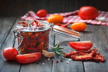 Sun-dried tomatoes with herbs and garlic in glass jar. Healthy food ingedients for delicous cooking. Rustic wooden background.
