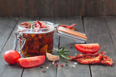 Sun-dried tomatoes with olive oil in glass jar, surounded with fresh and dry tomatoes, rosemary, garlic and pepper.
