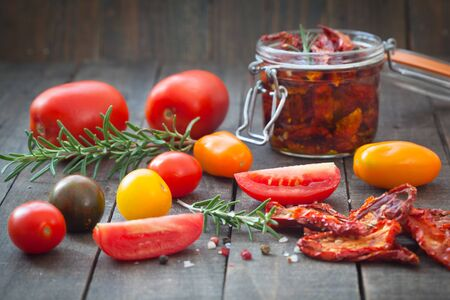 Sun dried tomatoes in olive oil with fresh herbs, spices and sea salt in a glass jar. Rustic wooden background.