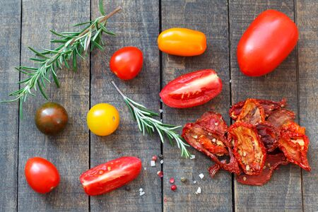Fresh and homemade dried tomato with spices and rosemary on wooden background. Colorful red, yellow and green tomatoes.