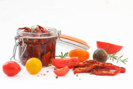 Sun dried tomatoes in olive oil with fresh herbs, spices and sea salt in a glass jar on white background. Healthy ingredients for delicious cooking food. 写真素材