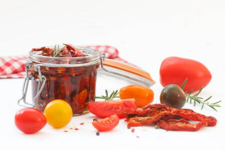 Sun-dried tomatoes with olive oil in glass jar, surounded with fresh and dry tomatoes, rosemary, pepper and sea salt. Healthy eating.