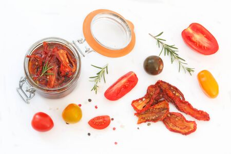 Sun-dried tomatoes with olive oil in glass jar, surounded with fresh and dry tomatoes, rosemary, pepper and sea salt. Healthy eating. Top view. 写真素材