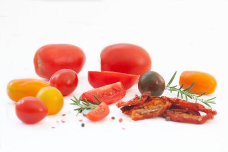 Fresh and homemade dried tomato with spices and rosemary on white background. Colorful red, yellow and green tomatoes.