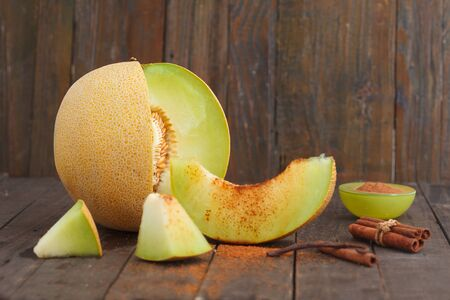 Cantaloupe melon and melon slices with cinnemon and brown sugar on wooden background. Refreshing slices of ripe, sweet melon.