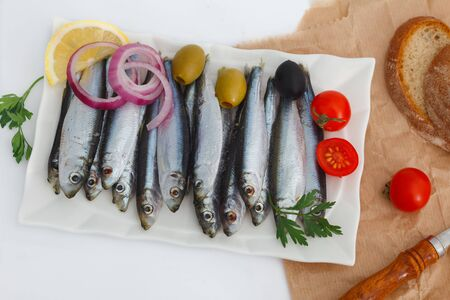 Blue sea fish, Sardines, ready for cooking with vegetables.  Healthy Sea food full of omega 3 fat.