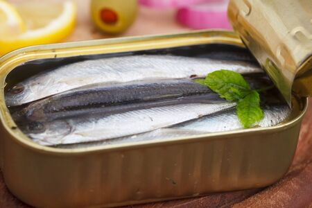 An opened can of sardines or herring in olive oil on wooden table. Healthy sea food full of omega 3 fats.