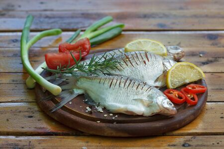 Carp fish on a wooden kitchen Board with lemons, spices and greens. Fish ready to cook.