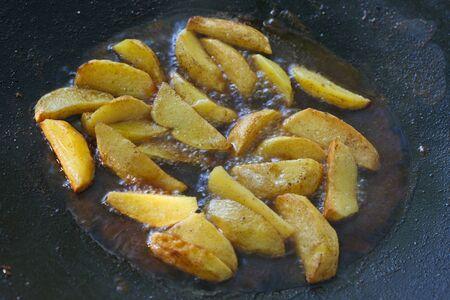 Frying potatoes in deep fat. Golden potato slies frying in a pan. Фото со стока