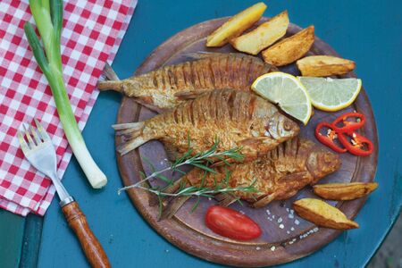 Fried carp fish served on a wooden plate with potato and decorated with rosemary and lemon. Healthy lunch in nature.Top view. 写真素材