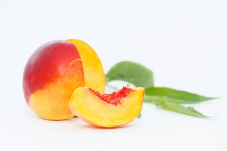 Delicious and juicy nectarina peach with leaves on white background. Healthy summer fruit. 写真素材