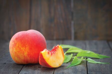 Fresh sweet peaches with one slice and green leaves on wooden table. Healthy summer fruit.