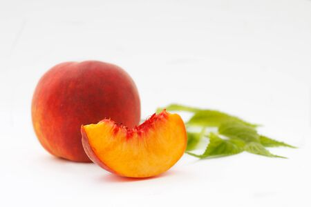 Delicious and juicy peach with leaves on white background. Healthy summer fruit. 写真素材