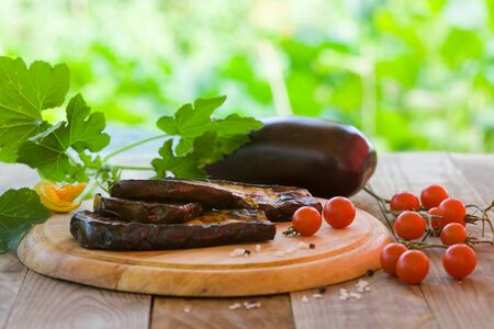 Slices of eggplant roasted on a grill, served with cherry tomato on a wooden board. Healthy vegetarian food.