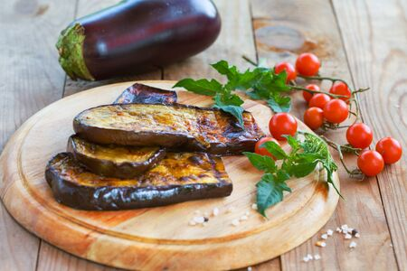 Delicious roasted eggplant and homemade cherry tomato on a wooden board. Healthy vegetarian food.