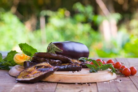 Delicious roasted eggplant and homemade cherry tomato on a wooden board. Healthy vegetarian food served in a garden.