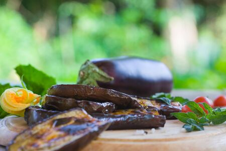 Slices of eggplant roasted on a grill, served with cherry tomato on a wooden table in a garden. Healthy vegetarian food.