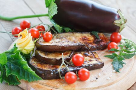 Delicious roasted eggplant and homemade cherry tomato on a wooden board. Healthy vegetarian food. Selective focus.