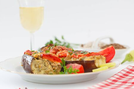 Baked eggplant or aubergine stuffed with minced meat and vegetables. Turkish or Greek homemade cuisine. Eggplant dish with vine on white background.