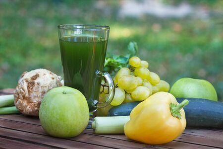 Healthy green smoothie with apples, grapes, cucumber and celery. Fruit and vegetable juice on wooden table, with blured nature in  background. Outdoor image.