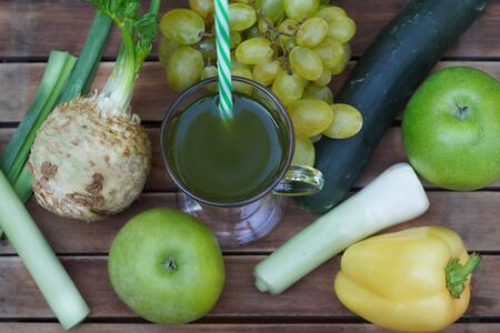 Healthy green smoothie with apples, grapes, cucumber, paprika and celery. Fruit and vegetable juice on wooden table, with blured nature in  background. Homemade green smoothie in glass with a straw. Top view.