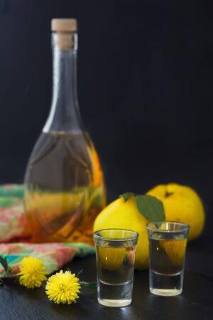 Quittenbrand oder Quittenwodka, Schnaps, starkes Getränk in einer Flasche und Gläser auf dunklem Hintergrund. Serebianischer traditioneller Dring, Rakija oder Rakia. Vertikales Bild.