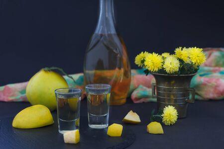 Quittenbrand oder Quittenwodka, Schnaps, starkes Getränk in einer Flasche und Gläser auf dunklem Hintergrund