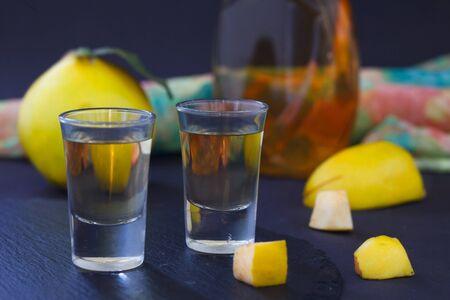 Quitte alkoholisches Getränk. Quittenbrand und frische Quitten auf dunklem Hintergrund. Serebianischer traditioneller Dring, Rakija oder Rakia. Standard-Bild