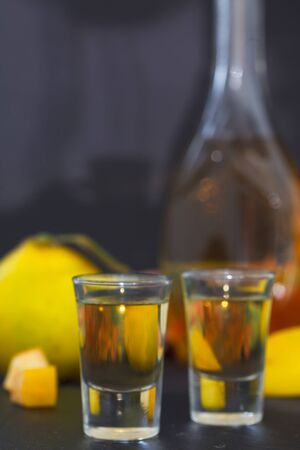 Quince alcoholic drink. Quince Brandy and fresh quinces on dark background, vertical image Standard-Bild