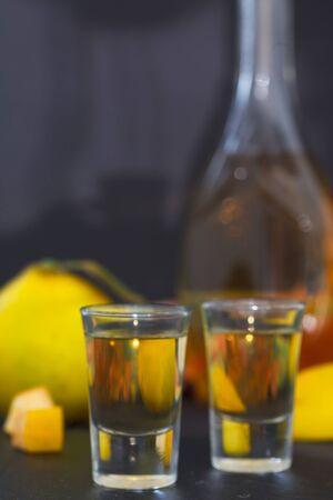 Quitte alkoholisches Getränk. Quittenbrand und frische Quitten auf dunklem Hintergrund, vertikales Bild