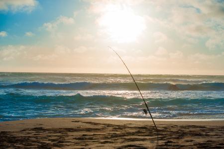 fishingpole: Fishing rods set up on beach shore at sunset Stock Photo
