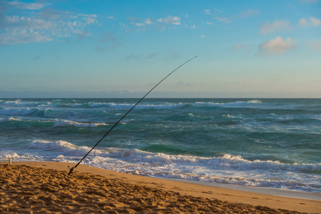 Fishing rods set up on beach shore at sunset Banque d'images