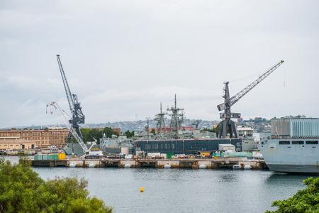 Military warship by a shipyard
