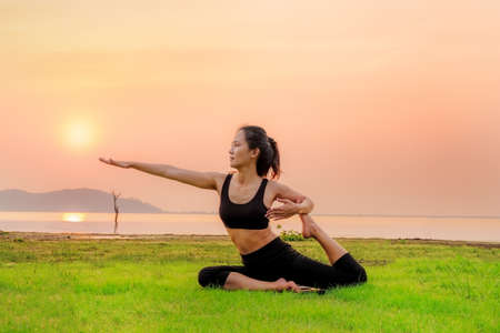 Yoga woman is relax on the fresh grass as floor.