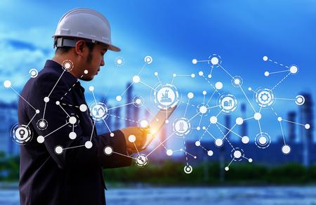 L'ingegnere sta lavorando con tabet su un background di grande industria. Il direttore dei lavori sullo sfondo del settore.
