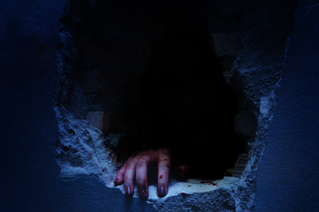 Horror Scene with bloody hand of evil is coming from a dark hole. Halloween concept.