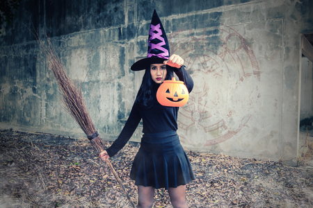 Young woman in witch Halloween costume hold a orange pumpkin over scary dark background. Stock Photo