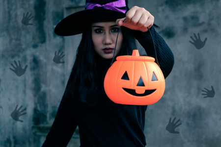 Young woman in witch Halloween costume hold a orange pumpkin over scary dark background. Standard-Bild